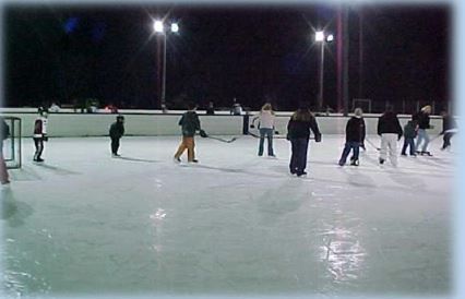 People playing hockey with the rink lights on